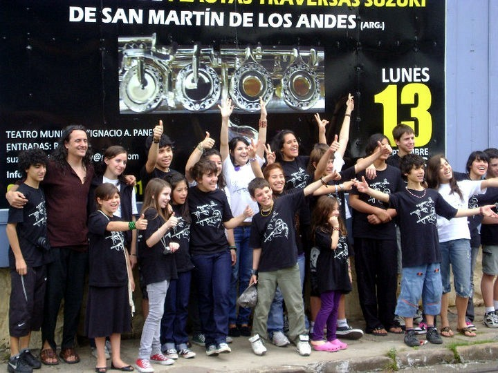 Fernando Formigo and flute group from Patagonia, Argentina in front of a billboard advertising their public concert in Asuncion, Paraguay