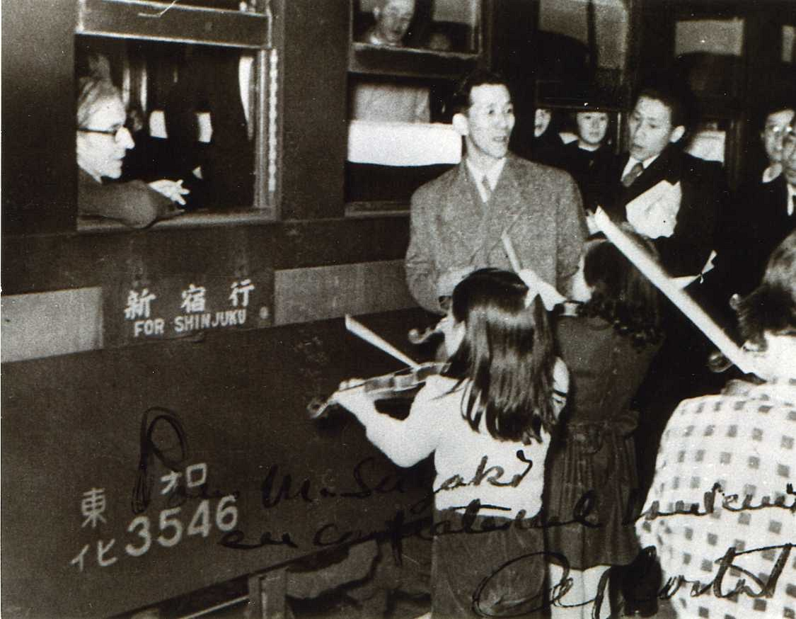 Shinichi Suzuki and students play at a railroad station for Alfred Cortot