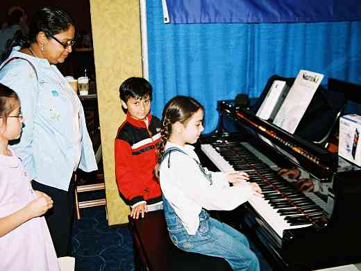 Trying out a piano in the exhibit area.