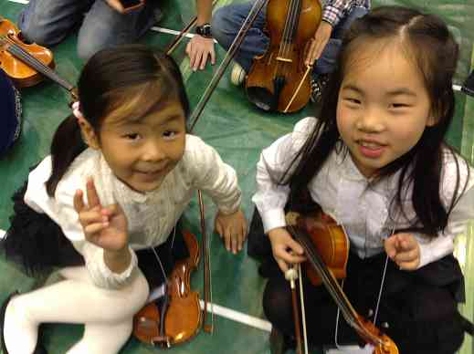 Two little girls from Taiwan waiting to have their instruments tuned at the Opening Ceremonies