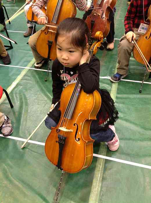 Cello student waiting to be tuned for the Opening Ceremonies