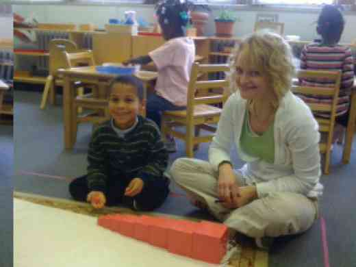 Montessori student with lead teacher Lisa Vukmirovich building pink tower blocks