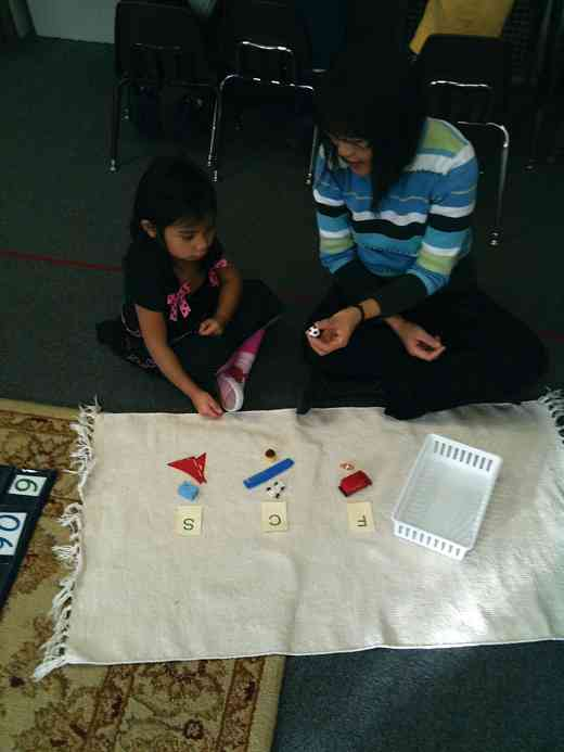 Montessori student with Wee Ling Sim, working on the sounds of the alphabet