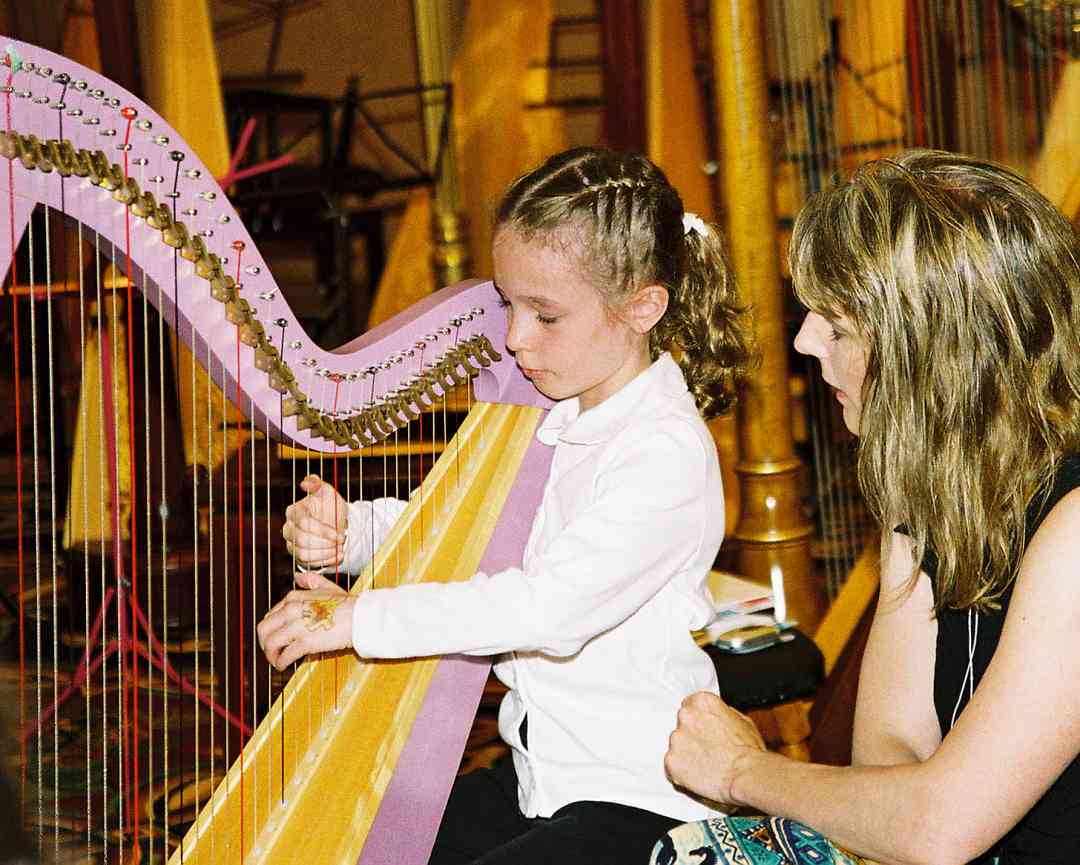 Jill Whitman with young harp student and pink harp.