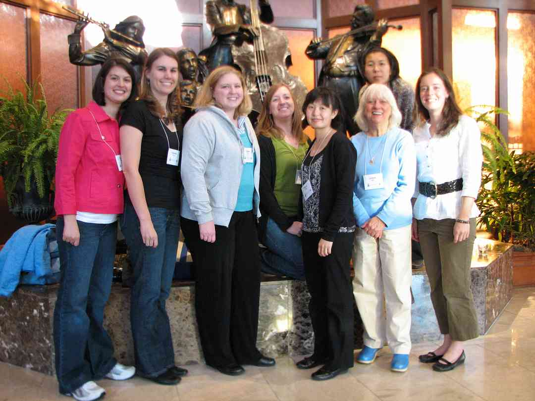 Joanne Bath and ECU past and current long-term training program participants with the Hilton lobby statues.