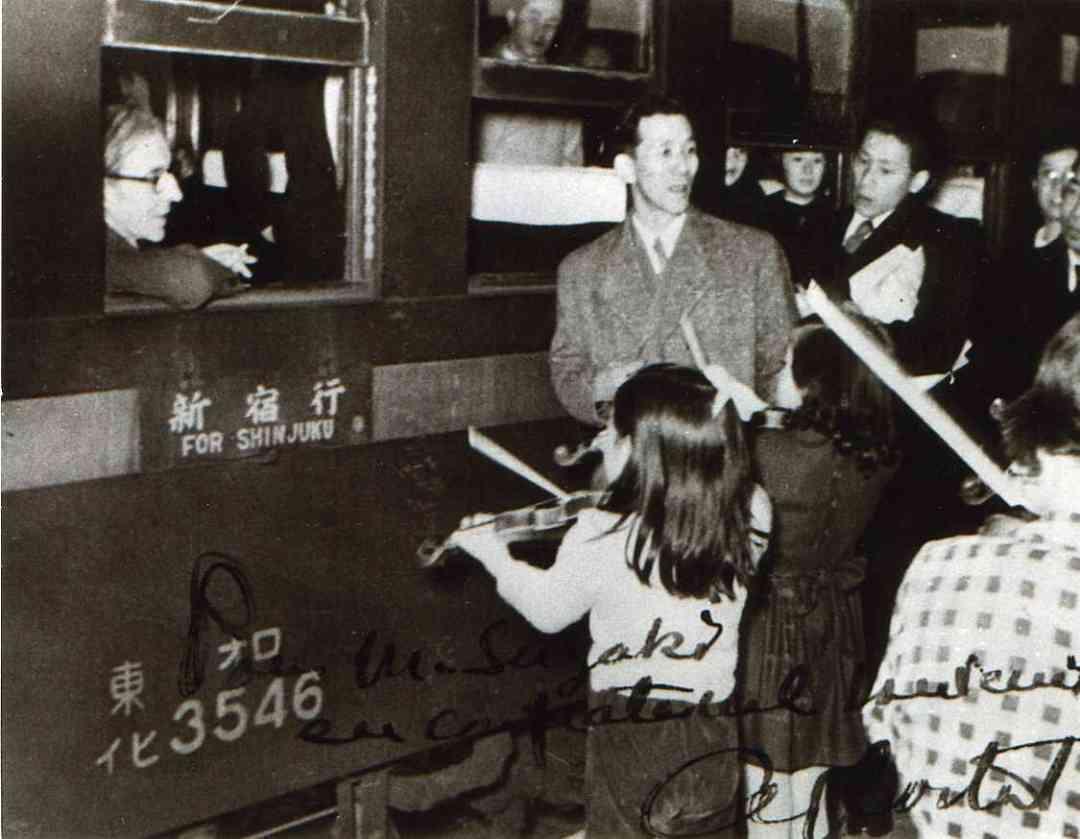 Shinichi Suzuki and students play at a railroad station for Alfred Cortot