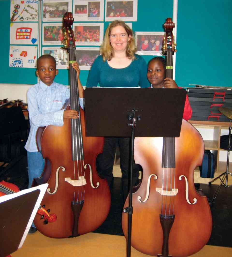 Two beginning bassists from Saint Ultans Cherry orchard with bass teacher Eimear Saunders